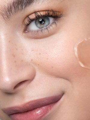 Close up studio shot of a beautiful woman with perfect freckled skin, applying foundation.